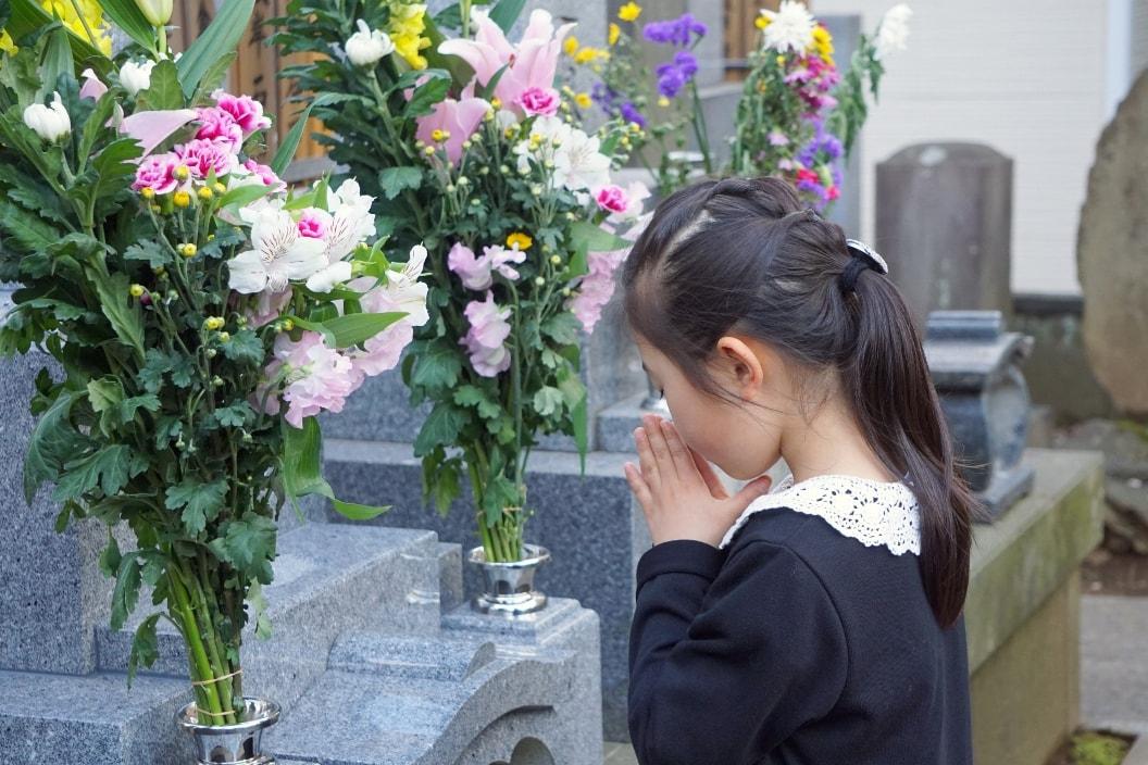 女の子がお墓参りしている画像